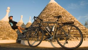 Cyclistresting against a trullo.