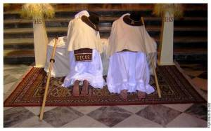 Masked men kneeling in front of the altar