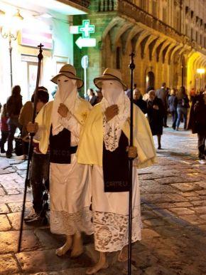 Caped men performing a Christian ritual
